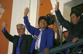 Bolivia's President Evo Morales greets supporters from the balcony of the presidential palace in La Paz, Oct. 12, 2014.