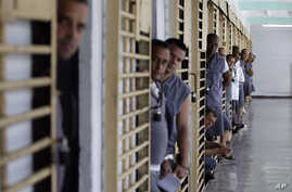 FILE - Prisoners look out from their cells at the Combinado del Este prison during a media tour in Havana, Cuba, Apr. 9, 2013.