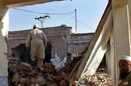 Pakistani men inspect the damage after suspected militants blew up a school building in Khyber region's Bara town, around 20 kilometers (13 miles) south of Peshawar, 21 Nov 2009