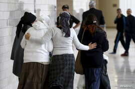 Israeli women, friends and relatives of two Jewish citizens who, according to Israel Radio, were indicted for a July 31 arson attack, walk together outside a courtroom at the District court in Lod, central Israel, Jan. 3, 2016.