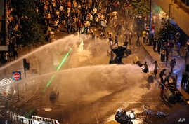 Lebanese activists shout anti-government slogans as they are sprayed by riot police using water cannons during a protest against the ongoing trash crisis, in downtown Beirut, Lebanon, Sunday, Aug. 23, 2015.