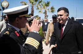 This image released by the media office of the unity government shows Fayez al-Sarraj, right, upon his arrival in Tripoli, Libya, March 30, 2016. He arrived by sea with six deputies to set up a temporary seat of power in a naval base.