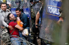 Migrant men help a fellow migrant man holding a boy as they are stuck between Macedonian riot police officers and migrants during a clash near the border train station of Idomeni, northern Greece, as they wait to be allowed by the Macedonian police t