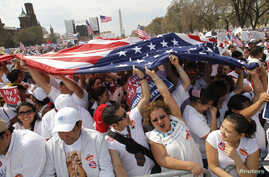 Immigration reform demonstrators carry a U.S. flag as they chant slogans during a mass rally for comprehensive immigration policy reform on the Washington Mall, March 21, 2010. While the House of Representatives holds its most critical vote on histor