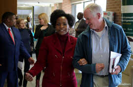 Malcolm McGowan, father of South African Stephen McGowan, who was kidnapped by al-Qaida from Timbuktu in 2011 and has been released and is back home, chats to Foreign Minister Nkoana-Mashabane after a media briefing in Pretoria, August 3, 2017.