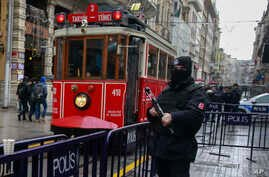 A tram drives past a Turkish police officer as he secures central Istanbul's Istiklal Avenue, the main shopping road of Istanbul, Jan. 5, 2017.