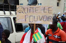 """A man holds up a sign which reads, """"leave the power,"""" during opposition protest to call for the immediate resignation of President Faure Gnassingbe in Lome, Togo, Sept. 7, 2017."""