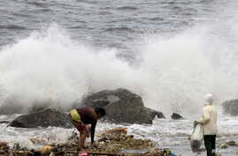 Residents collect recyclable materials from floating garbage found in the sea, while big waves crash along the coastline due to strong winds brought by Typhoon Goni, locally named as Ineng, at Manila bay, Aug. 22, 2015.