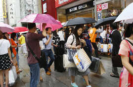 Chinese tourists with shopping bags wait for a sightseeing bus in front of a discount electronics store in Tokyo's Ginza district. The cheap yen, easier visas and other initiatives are luring foreign travelers eager to stretch their budgets and see s