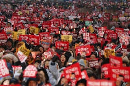 South Korean protesters hold placards during a rally calling for South Korean President Park Geun-hye to step down in Seoul, South Korea, Saturday, Nov. 26, 2016. For the fifth-straight weekend, masses of protesters are expected to occupy major avenu