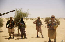 Fighters from Islamist group Ansar Dine stand guard during a hostage handover, in the desert outside Timbuktu, Mali, April 24, 2012.
