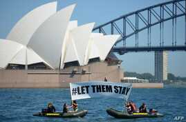 "Members of the environmental group Greenpeace hold up a sign that reads ""#LET THEM STAY"" in front of the Opera House in Sydney, Australia, Feb. 14, 2016."