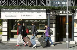 Asian tourists walk past a luxury watch shop in the Swiss alpine resort Interlaken, Switzerland, Nov. 17, 2015.