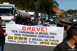 """Brazilian truck drivers blocked the BR-116 highway with their trucks during a strike in Curitiba, Brazil, May 21, 2018. The banner reads: """"Strike! Without truck, Brazil stop, we can not continue. Brazil will stop, total stoppage, support us!"""""""