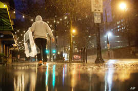 A person carries his dry cleaning while walking in the rain through midtown Atlanta, Wednesday, Dec. 23, 2015.