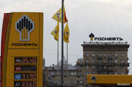 The logo of Russia's top crude producer Rosneft is seen on a price information board of a gasoline station in Moscow July 17, 2014.
