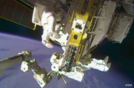 In this image taken from video provided by NASA, astronauts Rick Mastracchio, top, and Michael Hopkins work to repair an external cooling line on the International Space Station on Monday, Dec. 24, 2013, 260 miles above Earth. The external cooling li