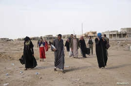 FILE - Displaced people leave al-Hud village, south of Mosul, during an operation to attack Islamic State militants in Mosul, Iraq, Oct. 18, 2016. Residents of al-Hud rose up against IS militants.