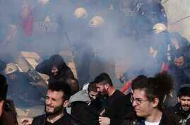 Police fire tear gas as protesters try to avoid it on the steps of parliament during a rally against a new austerity bill that will limit the right to strike and speed up property foreclosures, in Athens, Jan. 12, 2018.