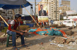 A supporter of deposed Egyptian President Mohamed Mursi guards outside one of the entrances of the sit-in area around Raba' al-Adawya mosque, where protesters are camping, east of Cairo, August 12, 2013.