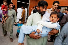 A man carries a child injured from an earthquake, in Peshawar, Pakistan, Oct. 26, 2015.