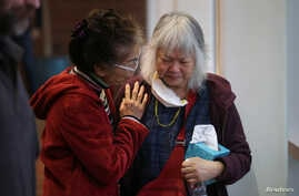 "A woman comforts Colleen Love, right, who lost her home in the Camp Fire, at a ""Thanksgiving Together"" dinner put on by World Central Kitchen at Chico State University in Chico, California, Nov. 22, 2018."