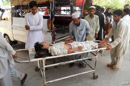 Pakistanis shift an injured bomb blast victim into a hospital in Kohat, July 18, 2012.