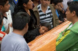 A girl embraces the coffin with the body of Yalid Jimenez, 29, who died Sunday during the clearing of the highway in Nochixtlan, Mexico, June 20, 2016. Violence erupted during the weekend in confrontations between the police and striking teachers.