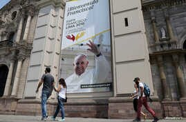 People walk past Lima Cathedral with a banner of Pope Francis before his visit to Peru, Jan. 18-21, in Lima, Peru, Jan. 12, 2018.