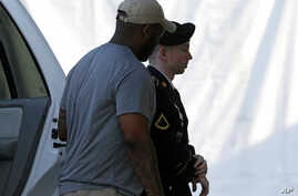 Army Pfc. Bradley Manning, right, is escorted into a courthouse in Fort Meade, Md., before a court martial hearing, July 18, 2013.
