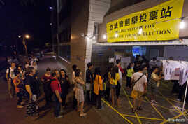 People queue as they wait to cast their votes at a polling station in Hong Kong September 9, 2012. Hong Kong residents voted for a new legislature on Sunday, a day after the territory's Beijing-backed leader backed down on a plan to introduce a compu