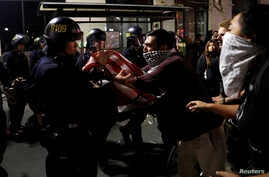 A masked demonstrator scuffles with police officers during a demonstration following the election of Donald Trump as president of the United States, in Oakland, California, Nov. 10, 2016.