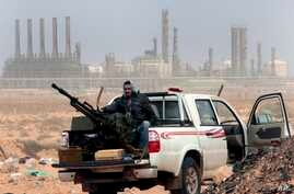 Libya Oil: FILE - In this March 5, 2011 file photo, an anti-government rebel sits with an anti-aircraft weapon in front an oil refinery in Ras Lanouf, eastern Libya.