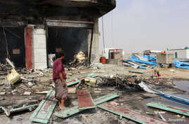 A man stands at the scene of an airstrike that hit a truck at a petrol station in Abss, Yemen, April 24, 2018.