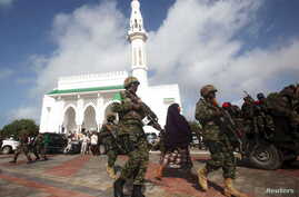 Soldiers serving in the African Union Mission in Somalia (AMISOM) patrol outside a Mosque during Eid al-Fitr prayers, marking the end of the fasting month of Ramadan at a Mosque in Somalia's capital Mogadishu, July 17, 2015.