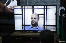 Saif al-Islam Gaddafi, son of deposed leader Muammar Gaddafi, is seen on a screen via video-link in a courtroom in Tripoli as he attends a hearing behind bars in a courtroom in Zintan, April 27, 2014.