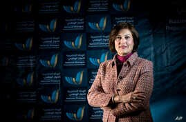 In this March 2014 image released by the National Dialogue Preparatory Commission, Salwa Bugaighis, lawyer and rights activist, poses for a photograph during a meeting in Tripoli, Libya