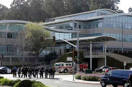 Law enforcement officials walk toward YouTube offices in San Bruno, Calif., April 3, 2018.
