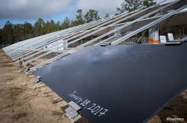 The first of the eventual 375,000 solar panels sits on it rack after a ceremonial initial installation ceremony at Eglin Air Force Base, Florida, Jan. 18, 2017.