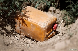 An improvised explosive device, discovered by Afghan National Army soldiers, is positioned in a hole before being detonated in the village of Khaleqdad Khan in Afghanistan's Zabul province May 26, 2012.