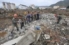 FILE - Workers recover cement blocks from flood-damaged areas in Onsong, North Hamgyong Province, North Korea, Sept. 16, 2016. Amid recent nuclear tensions, Pyongyang is struggling to secure aid for victims of flooding that occurred earlier this mont