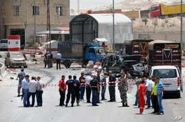 Lebanese army and plainclothes policemen gather at the site of an explosion near a police checkpoint in the eastern town of Dahr el-Baidar, Lebanon, Friday, June 20, 2014.