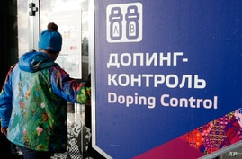 A man walks past a sign reading doping control, at the Laura biathlon and cross-country ski center, at the 2014 Winter Olympics in Krasnaya Polyana, Russia, Feb. 21, 2014.