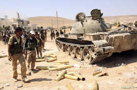 Free Syrian Army fighters inspect munitions and a tank that belonged to forces loyal to Syria's President Bashar al-Assad after they seized Khanasir, August 26, 2013.