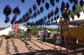 Workers hang lantern decorations at the entrance to the International Folk Art Market in Santa Fe, New Mexico, July 10, 2017.