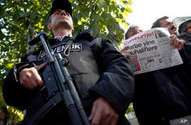 A man holds the latest copy of Cumhuriyet outside its headquarters after Turkish police detained the chief editor and several senior staff of Turkey's opposition newspaper in Istanbul, Oct. 31, 2016, amid growing fears over Turkey's widening crackdow