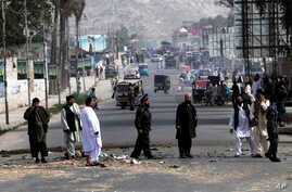 Afghan police officers inspect the scene after two bombs exploded at a Police checkpoint in the city of Jalalabad east of Kabul, Afghanistan, May 15, 2013.