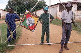 Police (R) and black squatters (behind the gate) guard the farm of expelled white farmer Rob Marshell, in Mazowe, some 60 km north of Harare, Zimbabwe, April 10, 2000.