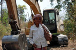 Puth La, 62, an ethnic minority Suy woman, standing next to a digger that villagers say is being used by a Singaporean company in the province of Kampong Speu, three hours drive south-west of the capital Phnom Penh, Cambodia, 17 Feb 2010