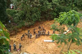 Indian Army soldiers dig at the site of a mudslide as they look for bodies of missing people in Tamenglong district, in the northeastern Indian state of Manipur, July 11, 2018.